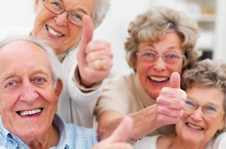 group of smiling aged men and women giving thumbs up
