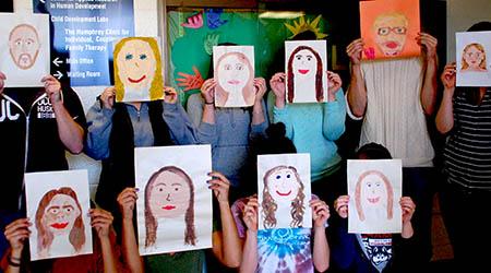 ECS teachers with painted self portraits